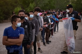 Unaccompanied minors from Central America line up to be transported by U.S. Customs Border Protection officials, after crossing…