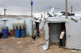 FILE PHOTO: A Syrian refugee boy stands in front of a tent at an informal tented settlement in the Bekaa valley, Lebanon March…