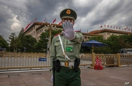A Chinese People's Liberation Army (PLA) soldier wearing a protective face mask gestures to the photographer to stop taking…