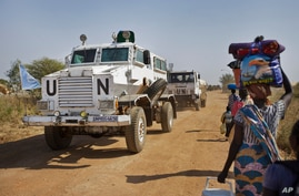 FILE - In this Monday, Dec. 30, 2013 file photo, a United Nations armored vehicle passes displaced people walking towards the U…