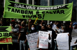 """Demonstrators hold Portuguese messages like """"Saving jobs is also saving lives"""" outside a city government office to protest a two-week-long lockdown to curb the spread of COVID-19 in Brasilia, Brazil, March 1, 2021."""