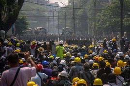 Anti-coup protesters, behind makeshift barricades stand off with Myanmar security forces in Yangon, Myanmar, March 2, 2021.