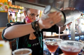 Bartender Alyssa Dooley makes a cocktail at Mo's Irish Pub, Tuesday, March 2, 2021, in Houston. Texas Gov. Greg Abbott…