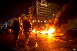 Protesters smoke water pipes in front burning tires that were set on fire to block a road, at Martyrs Square, in downtown…