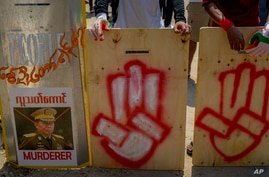 Anti-coup protesters stand behind a line of makeshift shields marked with three-fingered salute and defaced image of Commander…
