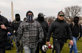 In this Jan. 6, 2021, photo, Proud Boy members Joseph Biggs, left, and Ethan Nordean, right with megaphone, walk toward the U.S…