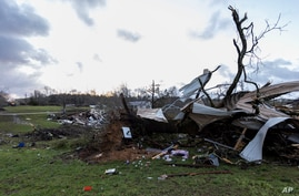 The sun rises over weather-damaged properties at the intersection of County Road 24 and 37 in Clanton, Ala., following a large outbreak of severe storms across the southeast, March 18, 2021.