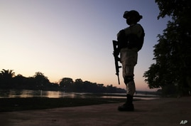 FILE - A Mexican National Guard stands on the bank of the Suchiate River, the natural border with Guatemala near Ciudad Hidalgo, Mexico.