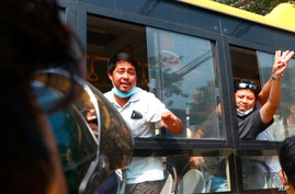 An arrested protester flashes the three-fingered salute while onboard a bus getting out of Insein prison to go to an…