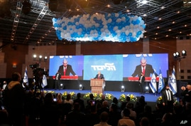 Prime Minister Benjamin Netanyahu address his supporters after the first exit poll results for the Israeli parliamentary…