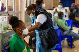 Khensani Chauke, a professional paramedic, receives a dose of Johnson & Johnson COVID-19 vaccine from a health staff member…