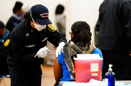 A member of the Philadelphia Fire Department administers a COVID-19 vaccine at a vaccination site in Philadelphia, Monday,…