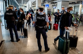 German federal police officers check passengers arriving from Palma de Mallorca for a negative Corona test as they arrive at the airport in Frankfurt, Germany, March 30, 2021.
