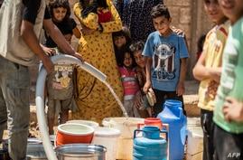 FILE - Residents fill up buckets with water from cisterns provided by humanitarian organisations during water shortages in Syria's northeastern city of Hasakah, Aug. 22, 2020.