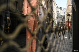 People walk near closed shops in Paris on March 20, 2021, on the first day of a new lockdown in France aimed to curb the spread of the COVID-19 cases.