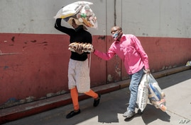 A woman walks with her blind husband as they carry food collected during a food distribution leaded by the international NGO Gift to the Givers, in Johannesburg, South Africa, Oct. 14, 2020.