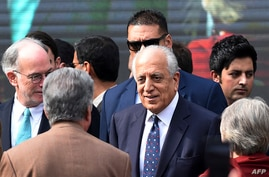 FILE - U.S. special envoy for Afghanistan Zalmay Khalilzad (C) arrives for a ceremony at the Presidential Palace in Kabul, March 9, 2020.