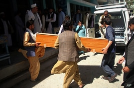 Afghans carry a coffin of the body of a woman who was killed by gunmen in the city of Jalalabad, east of Kabul.