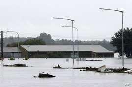 Debris floats past a partially submerged business flooded by water from the Hawkesbury River in Windsor, northwest of Sydney, New South Wales, Australia, March 22, 2021.