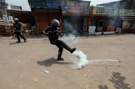 A policeman kicks away a tear gas shell that misfired while trying to disperse activists of Bangladesh Islamist group Hefazat-e-Islam,  enforcing a daylong general strike in Narayanganj, March 28, 2021.