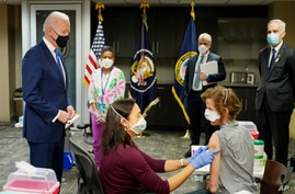 FILE - President Joe Biden, left, visits a COVID-19 vaccination site at the VA Medical Center in Washington, D.C., March 8, 2021.