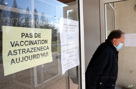 "A man leaves a vaccination site with a sign reading ""No vaccination with the AstraZeneca vaccine today,"" in Saint-Jean-de-Luz, southwestern France, March 16, 2021."