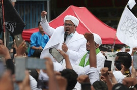 FILE - Hardline Islamic cleric Rizieq Shihab, center, speaks to his followers in Jakarta, Indonesia, Nov. 10, 2020.