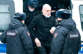 A man is being escorted out of a police van after he was detained in Moscow, Russia, March 13, 2021.