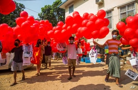 Anti-coup protesters hold red balloons carrying leaflets with various messages before releasing them during a gathering, in Yangon, Myanmar, March 24, 2021.
