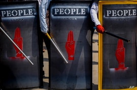 FILE - Anti-coup demonstrators hold makeshift shields during a protest in Yangon, Myanmar, March 9, 2021.