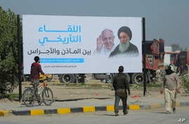 Iraqis walk by a poster announcing the upcoming visit of Pope Francis and his planned meeting with prominent Shiite Muslim leader, Ayatollah Ali al-Sistani, in Najaf, Iraq, March 3, 2021.
