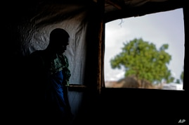 FILE - A South Sudanese refugee stands by a window, in Bidi Bidi, Uganda, June 3, 2017. A new report says South Sundanese activists abroad, including in Uganda, are being targeted by the government in Juba.