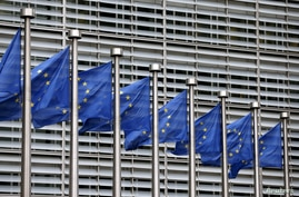 FILE - European Union flags flutter outside EU Commission headquarters in Brussels, Belgium, Oct. 28, 2015.