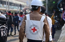 FILE - A Red Cross worker is seen amid protesters against the military coup, in Dawei, Myanmar, Feb. 28, 2021, in this photo obtained from social media. (Dawei Watch/via Reuters)