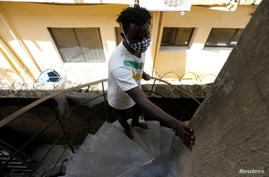 FILE - A visually impaired man climbs the stairs at a building where he lives, in Lagos, Nigeria, May 5, 2020.