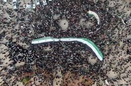 People carry Syrian opposition flags during a rally marking the 10th anniversary of the start of the Syrian conflict, in opposition-held Idlib, Syria, March 15, 2021.