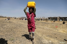 A girl carries a canister of cooking oil she received from the local charity Mona Relief at a camp for internally displaced people on the outskirts of Sana'a, Yemen March 1, 2021.
