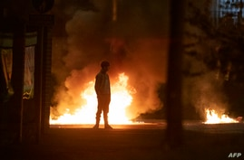 A boy stands and looks on as flames and smoke rises behind him at the scene of violence in Newtownabbey, north of Belfast, in…