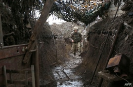 A Ukrainian serviceman walks along a trench at a position on the frontline with Russia-backed separatists near Gorlivka,…