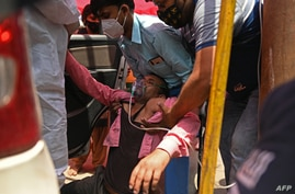 A patient breathes with the help of oxygen provided by a Gurdwara, a place of worship for Sikhs, outside a parked car along the…