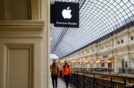 People pass by an Apple store at the State Department Store, GUM, in central Moscow on April 27, 2021. - Russia has imposed a …