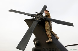 U.S. Army Specialist Nicole Derk of the C Company 3/82 Dustoff MEDEVAC performs a system check on a helicopter at the beginning…