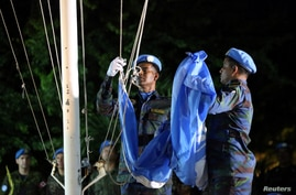 U.N. peacekeepers lower the U.N. flag during an event marking an end of the Mission of United Nations for the Stabilization in…