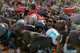 Migrant workers crowd up outside a bus station as they wait to board buses to return to their villages during a 21-day…