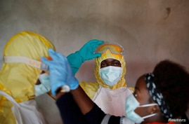 FILE - Healthcare workers adjust gear during funeral of person suspected of dying of Ebola in Beni, North Kivu.