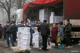 Local residents gather near a cargo trailer loaded with boxes containing food and personal hygiene products during the…