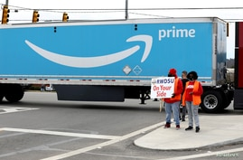 FILE PHOTO: People hold a banner at the Amazon facility as members of a congressional delegation arrive to show their support…