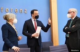 German Health Minister Jens Spahn, President of the Federal Union of German Associations of Pharmacists Gabriele Overwiening, and Vice-Chairman of the Federal Association of Pharmaceutical Wholesalers Marcus Freitag talk after a news conference in Berlin.