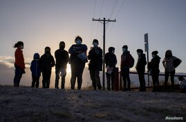 FILE PHOTO: Asylum seeking migrants from Central America await transport after crossing the Rio Grande river into the United…
