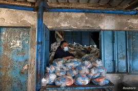 A Palestinian worker looks on as he prepares bags of food supplies at an aid distribution center run by United Nations Relief…